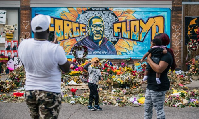 A family takes pictures in front of a separate mural of George Floyd in Minneapolis, Minn., on May 28, 2020. The mural looks similar to the one that collapsed on July 13 in Toledo, Ohio. (Brandon Bell/Getty Images)