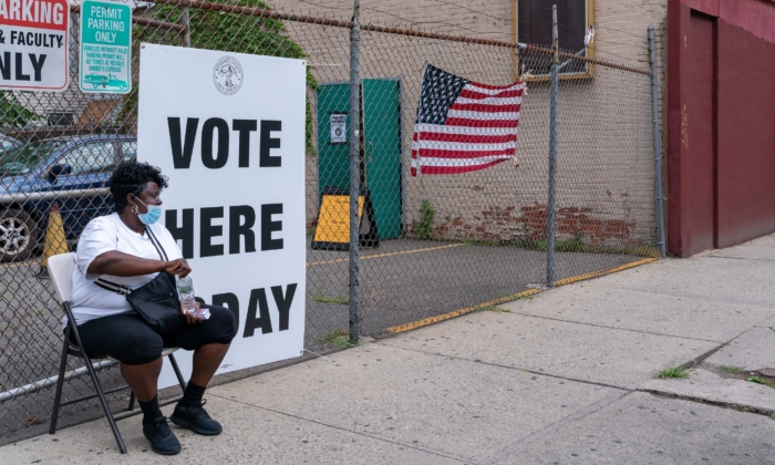 A poll worker sits outside of the polling station in Saint Aloysius in Jersey City, N.J., on July 7, 2020. (David Dee Delgado/Getty Images)
