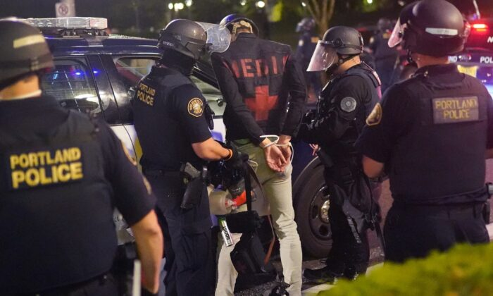 Portland police officers arrest a self-described medic amid rioting in Portland, Ore., early Aug. 21, 2020. (Nathan Howard/Getty Images)