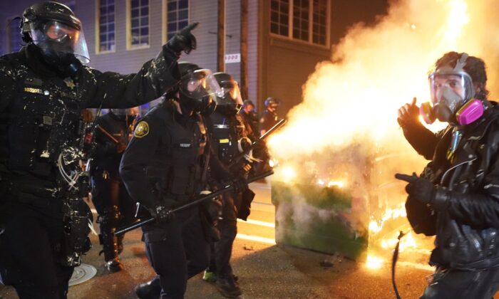 Portland police officers disperse rioters past a dumpster fire near the Immigration and Customs Enforcement detention facility in Portland, Ore., early Aug. 21, 2020. (Nathan Howard/Getty Images)