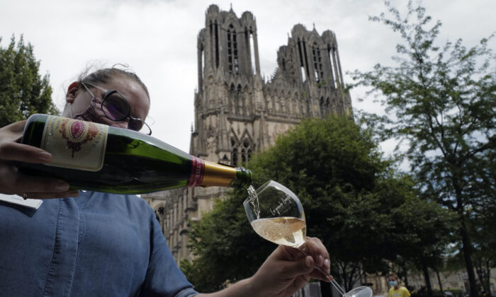 A waitress serves a glass of champagne at La Grande Georgette restaurant in front of the cathedral in Reims, the Champagne region. (AP Photo/Francois Mori)