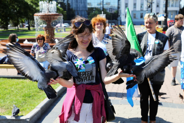A participant feeds pigeon anti-Kremlin rally-support of Sergei Furgal
