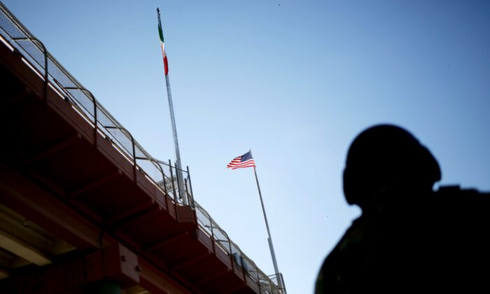 A U.S. flag and the Mexican flag are pictured on the international border bridge between El Paso, United States, and Ciudad Juarez, Mexico, on July 9, 2019. (Daniel Becerril/Reuters)