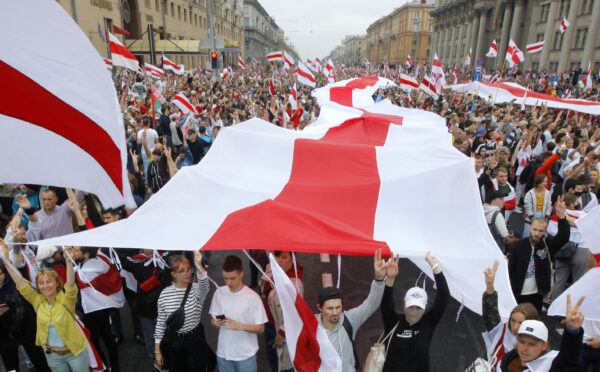Demonstrators carry a huge historical flag of Belarus