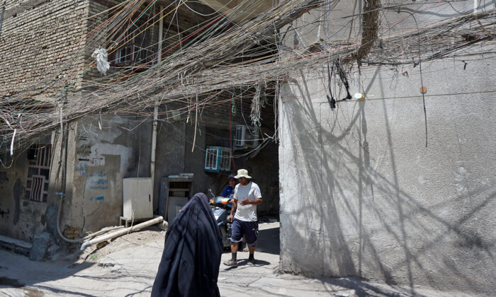 Iraqis walk beneath a web of electric wires in the Syed Sultan Ali area of the capital Baghdad, on July 13, 2020, used to draw electricity from private generators due to an unreliable national electricity supply amid high temperatures. (SABAH ARAR/AFP via Getty Images)