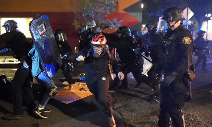 Protesters and Portland police clash while dispersing a crowd gathered in front of the Portland Police Bureau North Precinct early in the morning in Portland, Ore., on Aug. 22, 2020. (Nathan Howard/Getty Images)