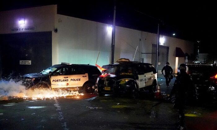 A smoke grenade ignites beneath a vandalized police cruiser at the Portland Police Bureau North Precinct during a protest in Portland, Ore., on Aug. 22, 2020. (Nathan Howard/Getty Images)
