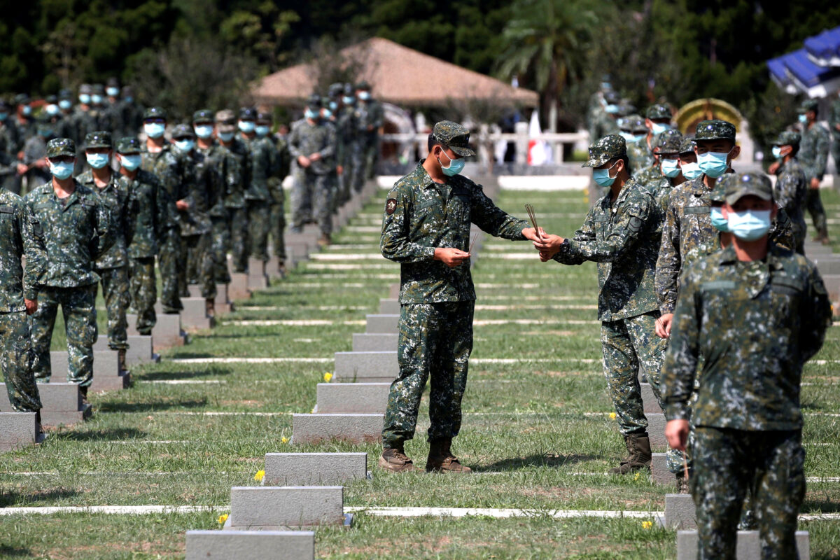 Soldiers pass incense to each other to pay respects to the deceased