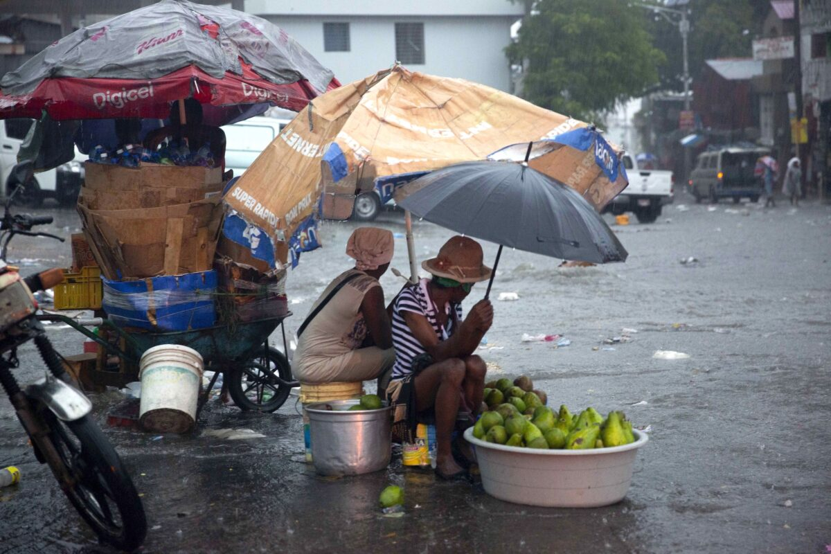 Street vendors protect themselves against the rain from Tropical Storm Laura