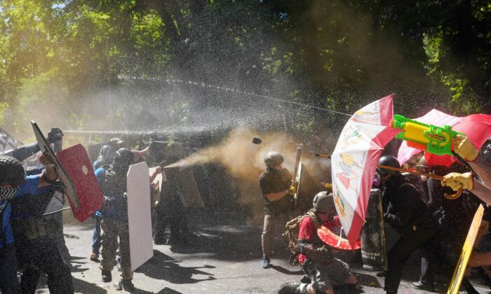 Pro-police demonstrators and others, left, and counter-protesters, fire pepper spray and hurl objects at each other in front of the Multnomah County Justice Center in Portland, Ore., on Aug. 22, 2020. (Nathan Howard/Getty Images)