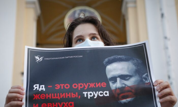 """A protester stands holds a poster reads """"poison is the weapon of a woman, a coward and a eunuch!"""" during a picket in support of Russian opposition leader Alexei Navalny in the center of St. Petersburg, Russia, on Aug. 20, 2020. (Elena Ignatyeva/AP Photo)"""