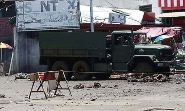 A military truck lies at an area where a bomb exploded at the town of Jolo, Sulu province, southern Philippines, on Aug. 24, 2020. (Philippine National Red Cross via AP)