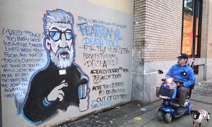 A man stops to read a mural about the fentanyl and opioid overdose crisis, in the Downtown Eastside of Vancouver, in a file photo. (Darryl Dyck/The Canadian Press)