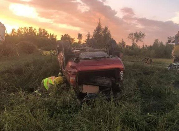 A first responder checks on an overturned vehicle at the scene where a tornado touched down, uprooting trees and overturning two vehicles near Virden, Man., Aug. 7, 2020. (The Canadian Press/HO-Wallace District Fire Department)