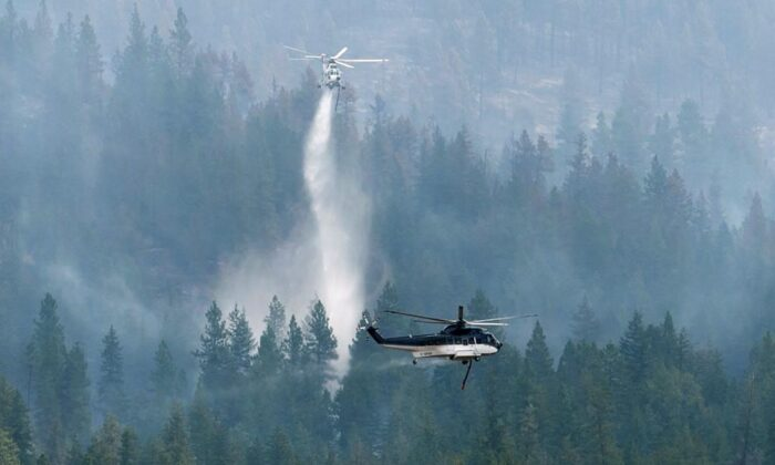 Helicopters drop water on the Christie Mountain wildfire along Skaha Lake in Penticton, B.C., on Aug. 21, 2020. (The Canadian Press/Jonathan Hayward)