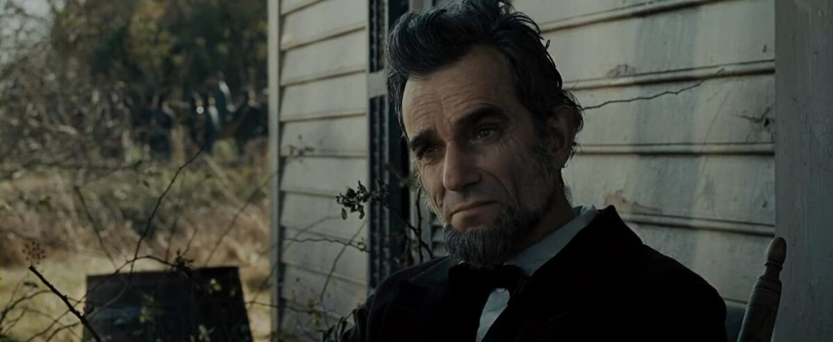 "man sitting on porch in ""Lincoln"""