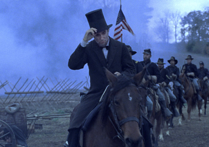 "man in top hat rides horse in ""Lincoln"""
