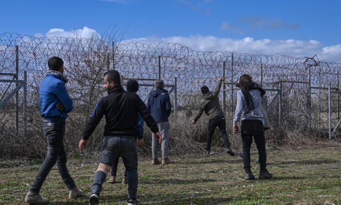 Migrants stand near the border fence on the Turkey-Greece border buffer zone near Pazarkule crossing gate in Edirne, Turkey, on March 7, 2020. (Ozan Kose/AFP via Getty Images)