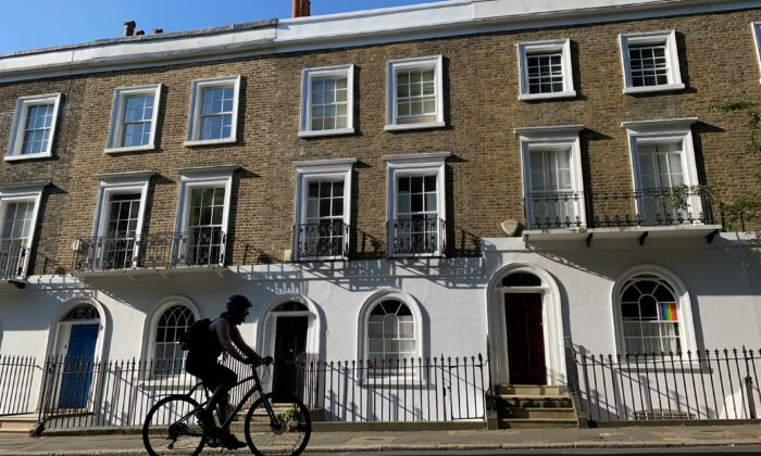 A person on a bicycle rides past houses on a street in Islington, London, on June 22, 2020. (Simon Newman/Reuters)