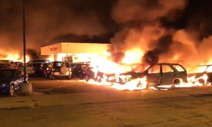 A car dealership burns after being set on fire amid rioting in Kenosha, Wis., early Aug. 24, 2020. (Drew Hernandez/@livesmattershow)