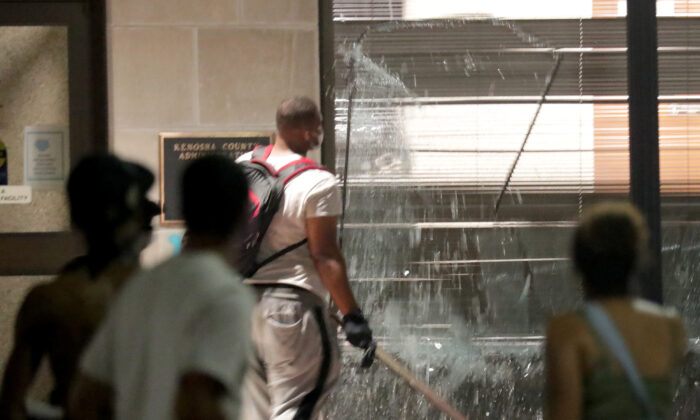Rioters smash windows at the Kenosha County Administration Building during unrest following the police shooting of Jacob Blake in Kenosha, Wis., on Aug. 23, 2020. (Mike De Sisti/Milwaukee Journal Sentinel via USA TODAY via Reuters)