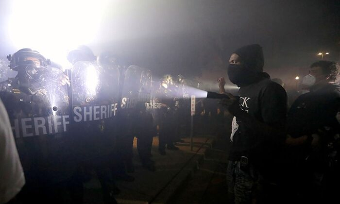 A protester shines a flashlight in the direction of Kenosha County sheriff's deputies outside the Kenosha Police Department in Kenosha, Wisconsin. (Reuters)
