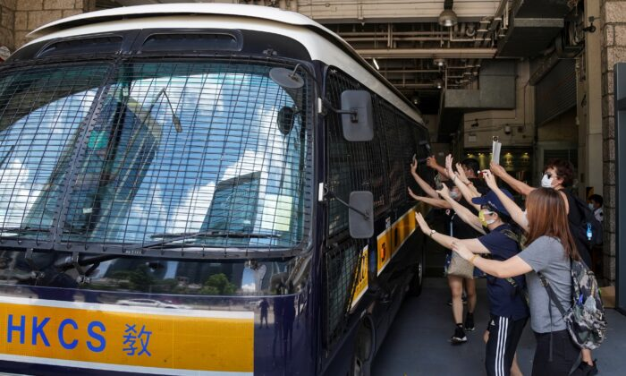 Supporters bid farewell to a prison van transporting Tong Ying-kit, a Hong Kong resident charged under the city's new national security law, who has been denied bail again in Hong Kong, China, on Aug. 25, 2020. (Lam Yik via Reuters)