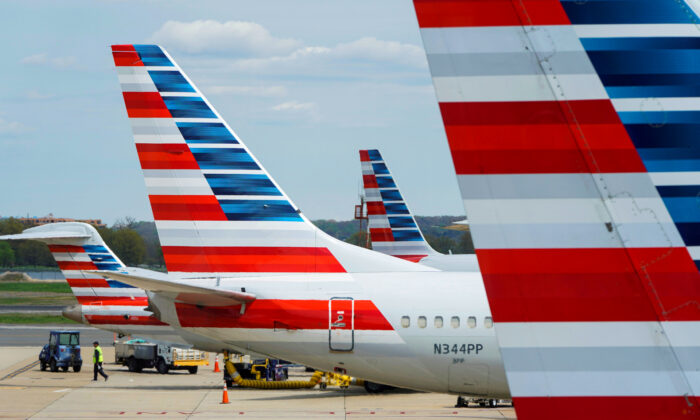 A member of a ground crew walks past American Airlines planes parked at the gate during the coronavirus disease (COVID-19) outbreak at Ronald Reagan National Airport in Wash., on  April 5, 2020. 