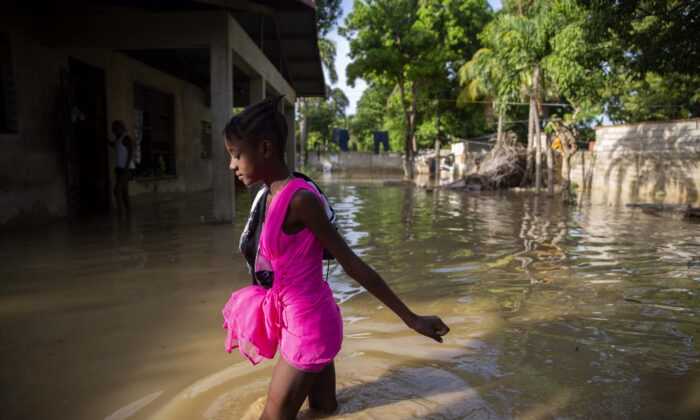 A girl wades towards her flooded home the day after the passing of Tropical Storm Laura in Port-au-Prince, Haiti, on Aug. 24, 2020. (Dieu Nalio Chery via AP Photo)
