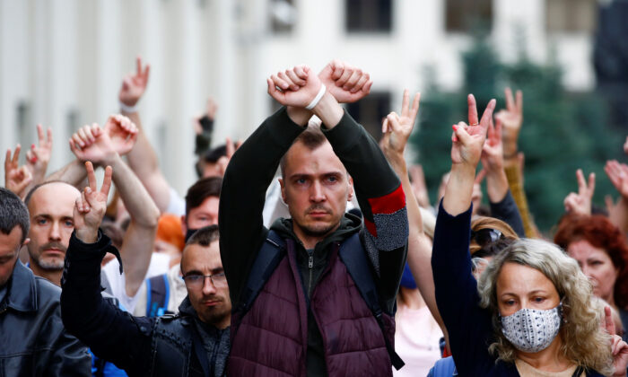 People gesture as they take part in a rally against presidential election results near the Ministry of Education in Minsk on August 25, 2020. (Vasily Fedosenko/Reuters)