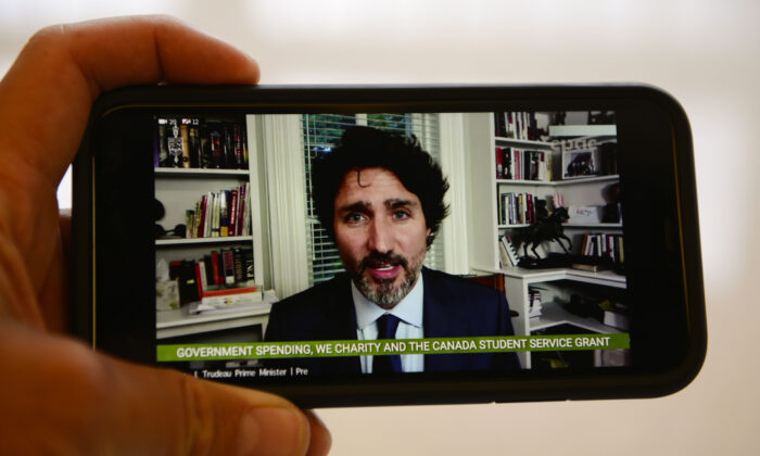 Prime Minister Justin Trudeau is viewed on a mobile phone as he appears as a witness via videoconference during a House of Commons finance committee in the Wellington Building on Thursday, July 30, 2020. The committee is looking into Government Spending, WE Charity and the Canada Student Service Grant.  THE CANADIAN PRESS/Sean Kilpatrick