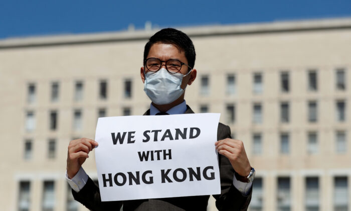 Exiled Hong Kong pro-democracy activist Nathan Law holds a placard outside the Italian Foreign Ministry, ahead of a meeting between Italian Foreign Minister Luigi di Maio and his Chinese counterpart, Wang Yi, in Rome, Italy, on Aug. 25, 2020. (Yara Nard/ Reuters)