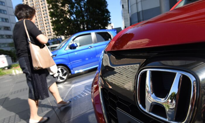 A woman walks past vehicles by Japan's Honda Motor at the company's headquarters in Tokyo, Japan, on May 13, 2016. (Toru Yamanaka/AFP via Getty Images)