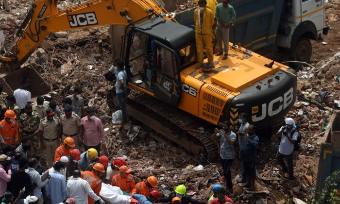 National Disaster Response Force (NDRF) officials carry a dead body which was recovered from the debris after a five-storey building collapsed in Mahad in Raigad district in the western state of Maharashtra, India, on Aug. 25, 2020. (Francis Mascarenhas/Reuters)