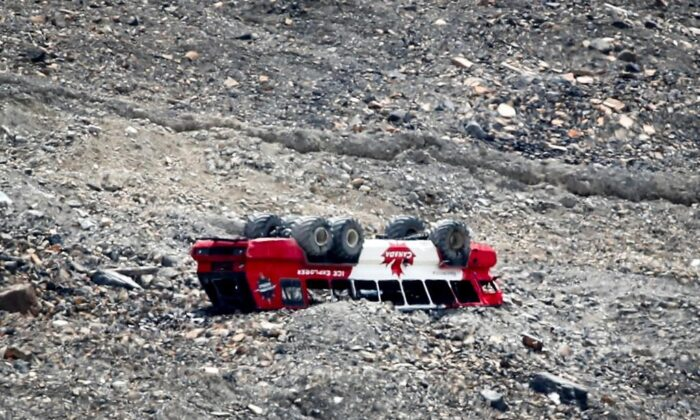 A rolled-over tour bus rests where it fell on the Columbia Icefield near Jasper, Alta., July 19, 2020. A class-action lawsuit alleging the defendants acted recklessly and unreasonably has been filed against the operators of a tour bus involved in a fatal rollover at Jasper National Park's Columbia Icefield. (Jeff McIntosh/The Canadian Press)