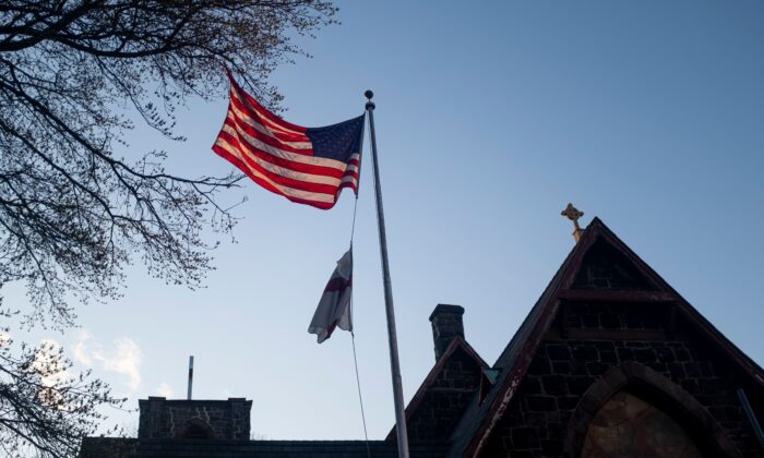 "A U.S. flag is lit by the setting sun in front of the Church of the Redeemer next to the Mount Sinai Hospital in Queens, New York City, on April 15, 2020. The CCP virus pandemic is likely to have a ""profound and pervasive impact"" on global mental health as billions struggle to cope with isolated living and anxiety spikes, experts warned. (Johannes Eisele/AFP/AFP via Getty Images)"