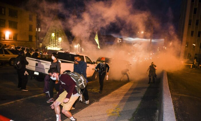 People run from tear gas thrown by the police near the Colorado State Capitol during rioting in Denver, Colo., on May 30, 2020. (Michael Ciaglo/Getty Images)