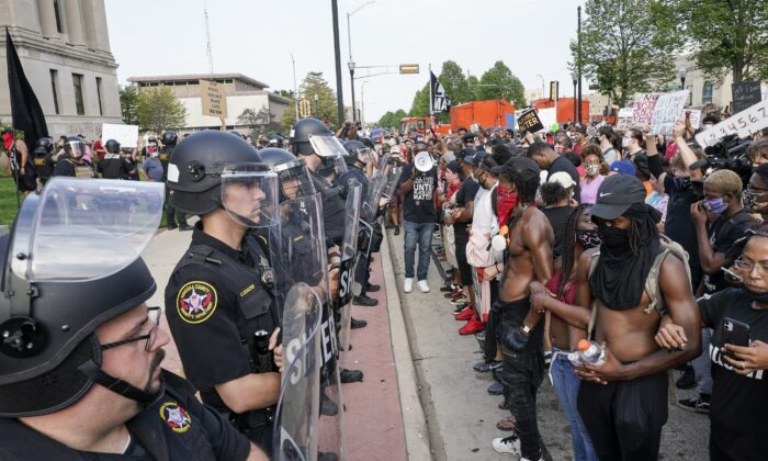 Protesters link arms in front of a police line outside the Kenosha County Courthouse in Kenosha, Wis., on Aug. 24, 2020. (Morry Gash/AP Photo)