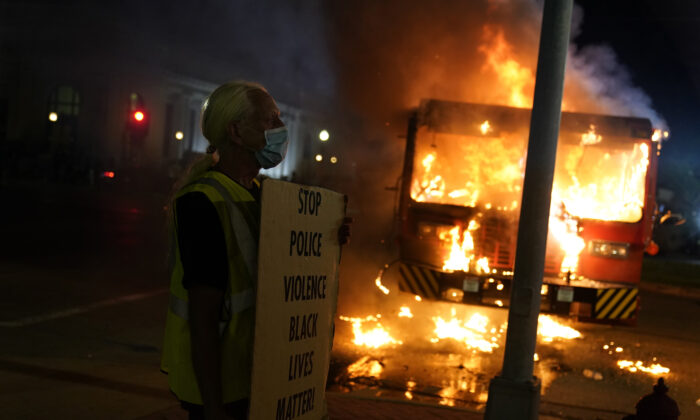 """A man stands with a """"Black Lives Matter"""" sign near a burning garbage truck in Kenosha, Wis., on Aug. 24, 2020. (Morry Gash/AP Photo)"""