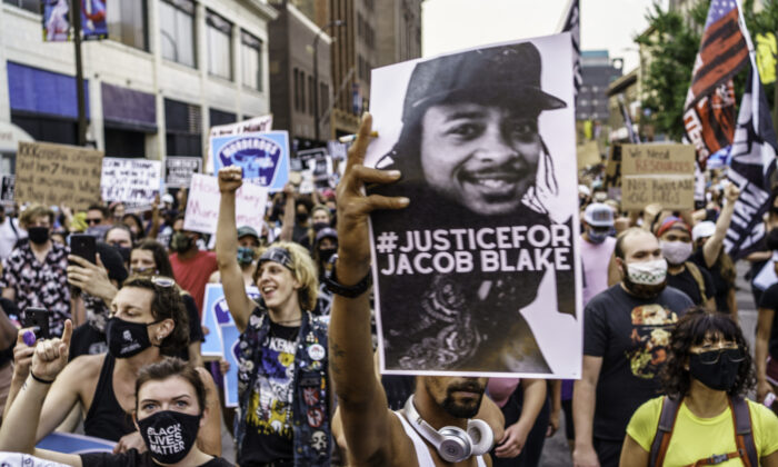Protesters march near the Minneapolis 1st Police precinct during a demonstration over the police shooting of Jacob Blake in Wisconsin, in Minneapolis, Minn., on Aug. 24, 2020. (Kerem Yucel/AFP via Getty Images)
