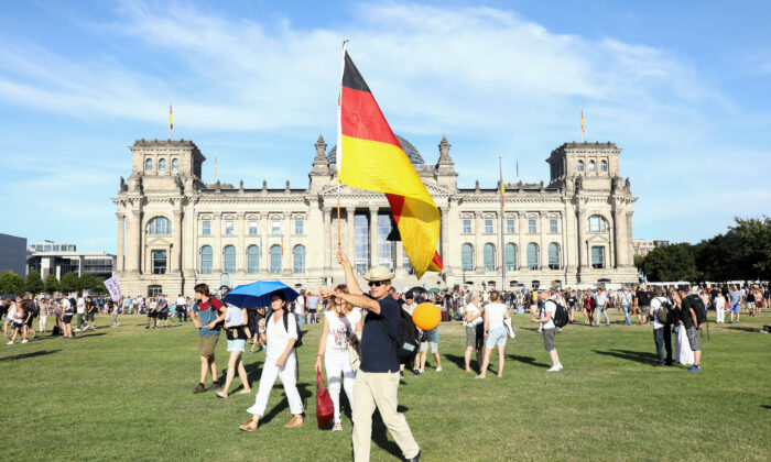 A demonstrator holds a German flag near the Reichstag during a protest against the government's restrictions imposed over the coronavirus outbreak, in Berlin, on Aug. 1, 2020. (Christian Mang/Reuters)