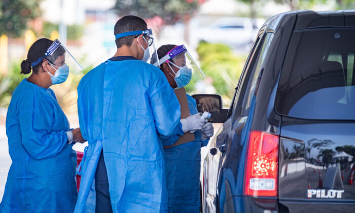 Health care workers administer a drive-through COVID-19 test at a new testing supersite at the Orange County Fair & Event Center in Costa Mesa, Calif., on Aug. 26, 2020. (John Fredricks/The Epoch Times)