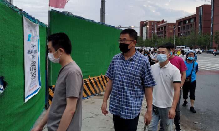 People wear protective masks as they wait in line to undergo COVID-19 coronavirus swab tests at a temporary test station in Beijing on July 6, 2020. (Lintao Zhang/Getty Images)