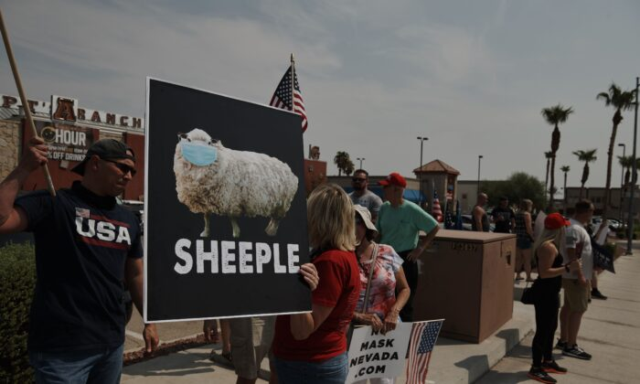 """Protesters rally against a mask mandate, many showing support for President Donald Trump, in Las Vegas, Nev., on Aug. 22, 2020. """"On day one"""" of his own presidency, Democratic presidential nominee Joe Biden said, he would implement a national COVID-19 plan and mandate mask wearing. (Bridget Bennett/AFP via Getty Images)"""