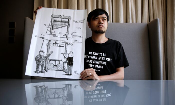 "Political illustrator Ah To poses with his work ""Guillotine"" after his cartoon column in one of the city's popular news magazines will get axed in Hong Kong, China, on July 28, 2020. (Tyrone Siu/Reuters)"