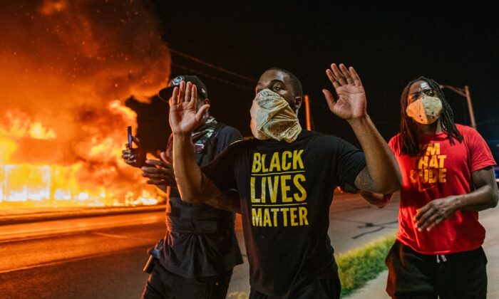 Men walk toward law enforcement with their hands up in Kenosha, Wis., on Aug. 24, 2020. (Brandon Bell/Getty Images)