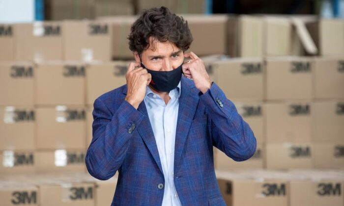 Prime Minister Justin Trudeau removes a cloth mask as he approaches the podium during an announcement at a factory in Brockville, Ont., on Aug. 21, 2020. (Adrian Wyld/The Canadian Press)