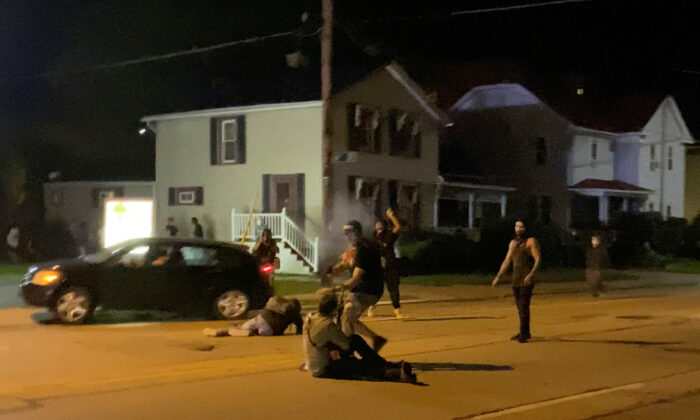 A man is being shot in his arm during a protest following the police shooting of Jacob Blake, in Kenosha, Wis., on Aug. 25, 2020. (Brendan Gutenschwager/via Reuters)