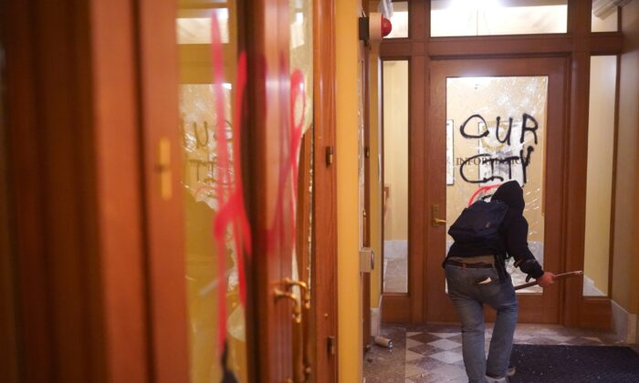A rioter runs through the vandalized lobby of City Hall in Portland, Ore., on Aug. 25, 2020. (Nathan Howard/Getty Images)