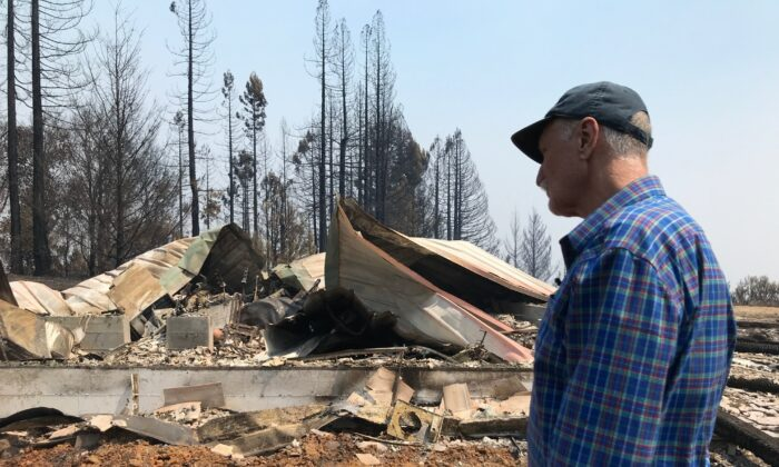 Charles Christianson, a 67-year-old retired school teacher returns to his destroyed home after a wildfire in Guerneville, Calif., on Aug. 25, 2020. (Aron Ranen via AP Photo)